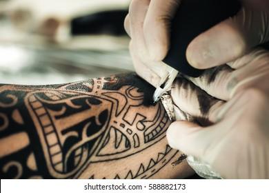 Master tattoo artist in gloves makes polynesian tattoo on hand men