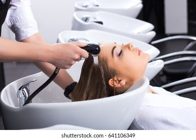 The master washes the blond girl's head in the beauty salon