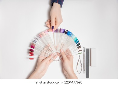Master woman manicurist chooses color of nail polish from palette with her finger. White isolated background. Top view.