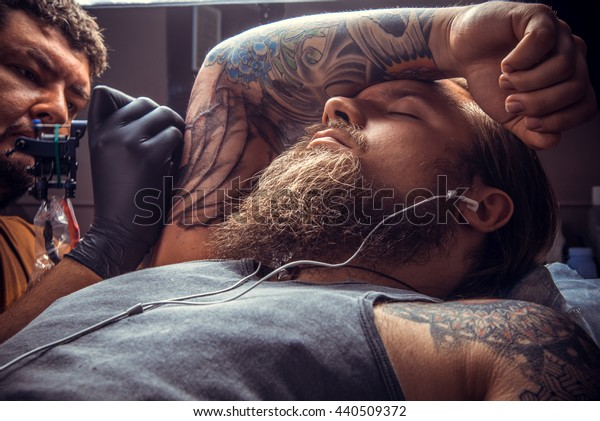 Master working tattooing in studio./Tattooist showing process of making a tattoo in salon.