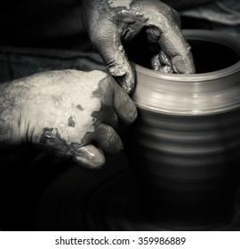 Master-ceramist creates a clay pot on a potter's wheel. Hands of potter close up, black and white photo in retro style. Ancient craft and pottery handmade work, vintage effect.