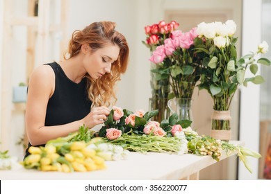 Masterclass of smiling florist at work with bunch of flowers. Florist at work: woman making bouquet of orange roses. Portrait of business woman florist working at flower shop