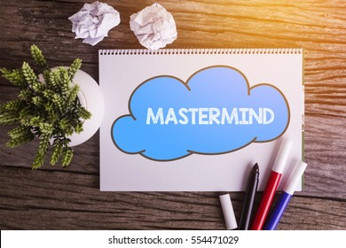 MASTERMIND word with Notepad and green plant on wooden background
