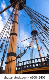Masts of the old historic wooden sailing ship on the blue sky background. Topmast, rigging, ropes and cables. Sea and ocean theme.