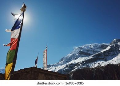 Masts with prayed flags in sunshine with snowy mountain in background. Upper Pisang, mountain village in Himalaya, Nepal. During trekking around Annapurna, Annapurna Circuit.