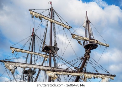 Masts and rigging of an old pirate ship on background of cloudy blue sky.