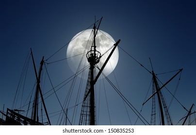 Masts silhouette of an old Portuguese caravel replica at full moon light.