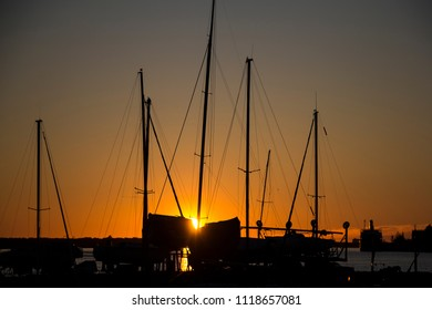 Masts of yachts on sunset background. Boat parking