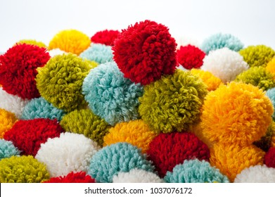 Mat of pompons made from multi-colored handmade yarn