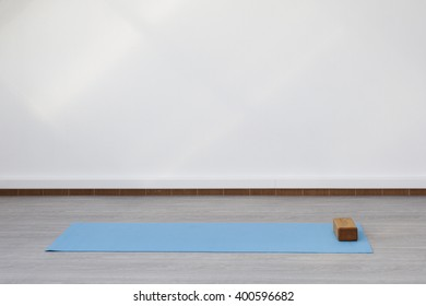 Mat and supporting unit for yoga and fitness lying on the floor. The room is flooded with daylight sunlight from the window, the glare on the white wall.