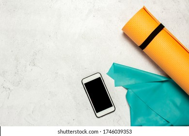 Mat for yoga and fitness, telephone, rubber harness for stretching on a light stone background. Fitness or yoga online concept. Banner. Copy space. Flat lay, top view