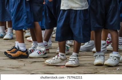 MATADI, DEMOCRATIC REPUBLIC OF CONGO - APRIL 22 2014: Legs with sneakers and school uniform pants of African pre school children