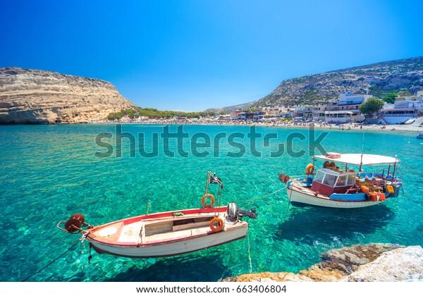 Пляж Матала со старыми рыбацкими лодками и пещерами на скалах, которые использовались в качестве римского кладбища и в десятилетие 70-х годов жили хиппи со всего мира, Крит, Греция