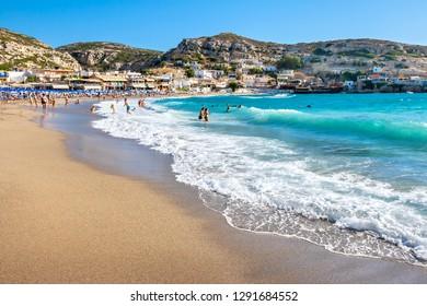 MATALA, CRETE, GREECE - JULY 25, 2011: Many people having fun on sandy beach at Matala village