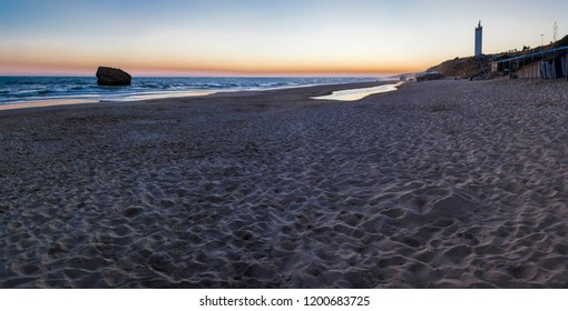 Matalacanas beach during the magnificent sunrise. Torre de la Higuera ruins and lighthouse, Costa de la Luz, Spain