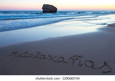 Matalacanas beach during the magnificent sunrise. Over the sand is written the name. Huelva, Spain
