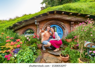 Matamata, New Zealand - February 12, 2017: Hobbiton Movie Set couple tourists taking selfie picture with phone in front of house door New Zealand travel vacation.