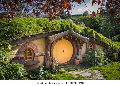 Matamata, New Zealand - July, 2018: Hobbiton movie set created to film Lord of the Rings and The Hobbit. Hobbit house with orange door.