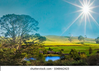 "MATAMATA- NEW ZEALAND-APRIL -19-2017:Hobbiton movie set created for filming the Lord of the Rings and ""Hobbit""movies- Matamata, New Zealand,Evening sky with sun flare,It is opened for tourist NZ"