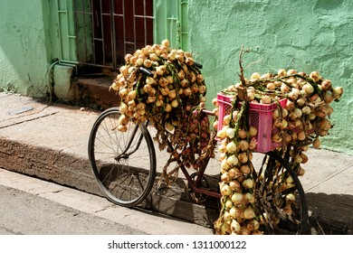 Matanzas, Republic of Cuba - 15.11.2017: Bike with lots of onions and pink basket in front of a green wall