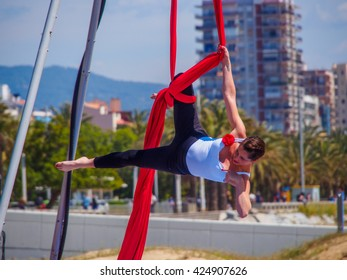 MATARO, BARCELONA, CATALONIA, SPAIN - MAY 2016: girl hanging from a rope doing acrobatics on the beach show