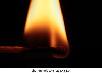 A match burning on a black background.