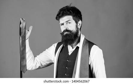 Match colors. Man bearded hipster hold few neckties on blue background. Guy with beard choosing necktie. Perfect necktie. For formal occasions choose solid colored tie that is darker than your shirt.
