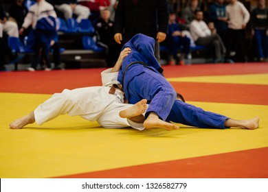 match judo judokas on tatami in gym with tribune audience
