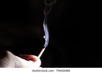 match, smoke on a dark background