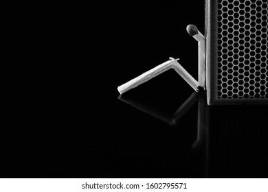 Match stick in thinking man style. Isolated black background. Match box. loneliness, sadness
