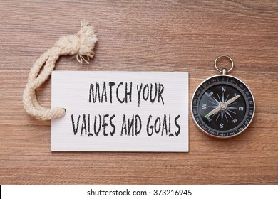 Match your value and goals -  inspirational advice handwriting on label with compass