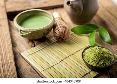 Matcha fine powdered green tea on wooden background.