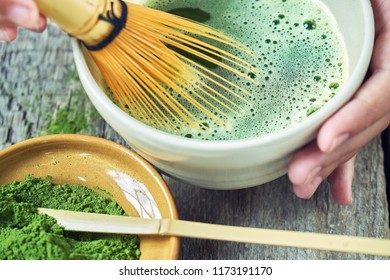 Matcha green tea accessoires on the rough wooden boards with girl's hands preparing matcha tea in the special clay bowl