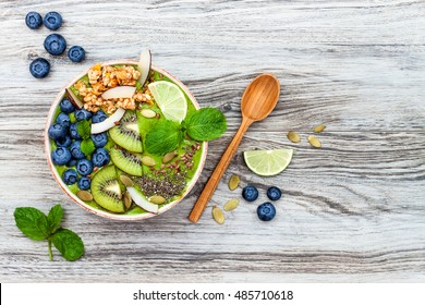 Matcha green tea breakfast superfoods smoothies bowl topped with chia, flax and pumpkin seeds, bee pollen, granola, coconut flakes, kiwi and blueberries. Overhead, top view, flat lay