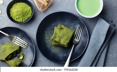 Matcha green tea cake, bars, brownie with white chocolate on a plate. Grey stone background. Top view.