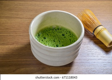 Matcha green tea in ceramic traditional chawan (tea bowl) with bamboo tea whisk on the wooden tray