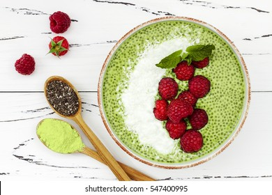 Matcha green tea chia seed pudding bowl, vegan dessert with raspberry and coconut milk. Overhead, top view, flat lay