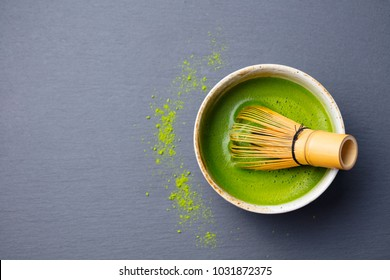Matcha green tea cooking process in a bowl with bamboo whisk. Black slate background. Top view. Copy space.