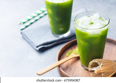 Matcha, green tea ice tea in tall glass on wooden plate. Grey stone background.