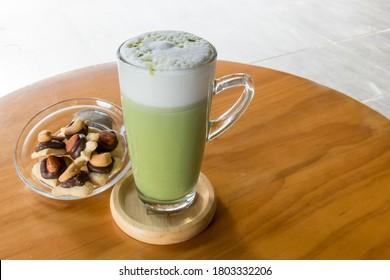 Matcha green tea latte beverage in glass mug with whisk. Matcha green tea latte beverage in glass mug.  Matcha Smoothie. This smoothie is made with powdered green tea