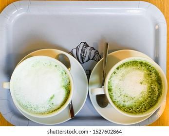 Matcha green tea latte. Cups of matcha tee with milk close up