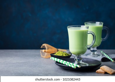 Matcha green tea latte with matcha powder and bamboo whisk. Grey stone background. Copy space.