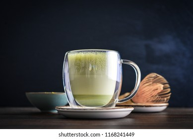 Matcha green tea latte with matcha powder and bamboo whisk on black  background closeup