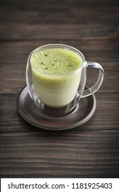 Matcha green tea latte with matcha powder and bamboo whisk on wooden background closeup