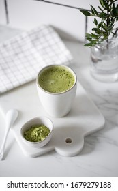 Matcha green tea latte in a rustic cup.