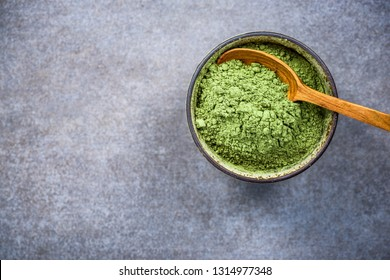Matcha green tea powder and bamboo spoon. Background with copy space.