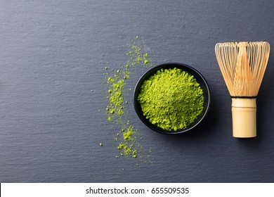 Matcha, green tea powder in black bowl with bamboo whisk on slate background. Top view. Copy space.