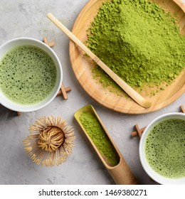 Matcha green tea ,powder matcha on a wooden round plate,welded powder in white Tawan,tasaku and a bamboo whisk on a light white concrete background