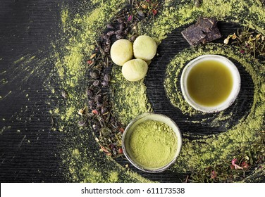 Matcha and green tea served with mochi over black wooden background. Top view