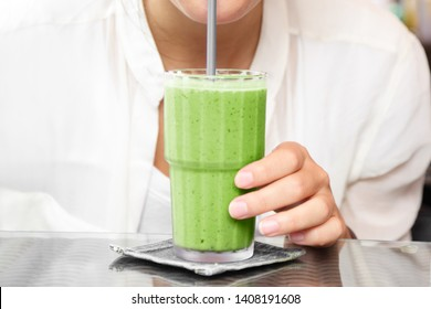 Matcha green tea smoothie cold dessert shake drink woman drinking with straw at cafe table.